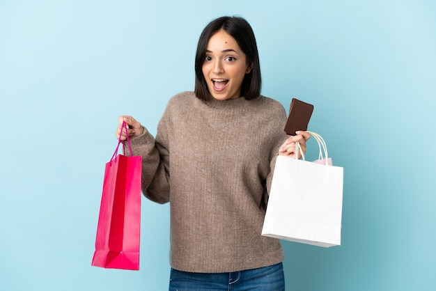 Giovane donna caucasica isolata sui sacchetti della spesa blu della tenuta e sorpresi