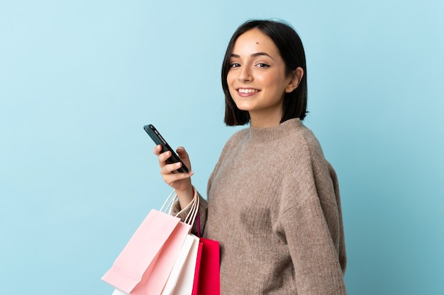 Giovane donna caucasica isolata sui sacchetti della spesa blu della tenuta e scrivendo un messaggio con il suo telefono delle cellule ad un amico