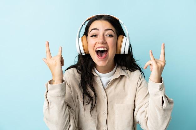 Giovane donna caucasica isolata sulla musica d'ascolto blu che fa gesto della roccia
