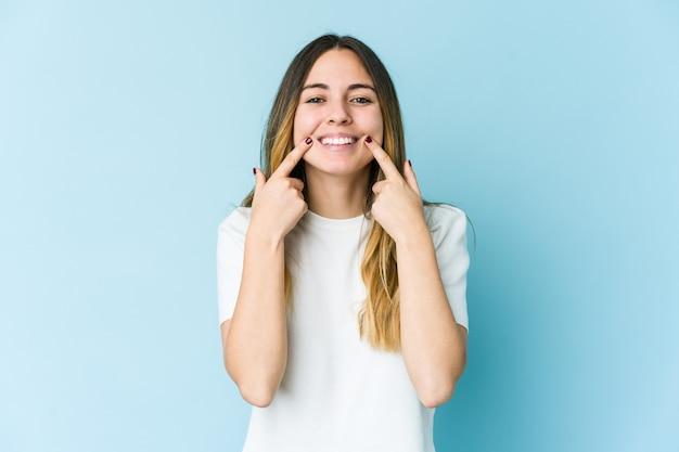 Giovane donna caucasica isolata su uno spazio blu sorride, puntando le dita alla bocca