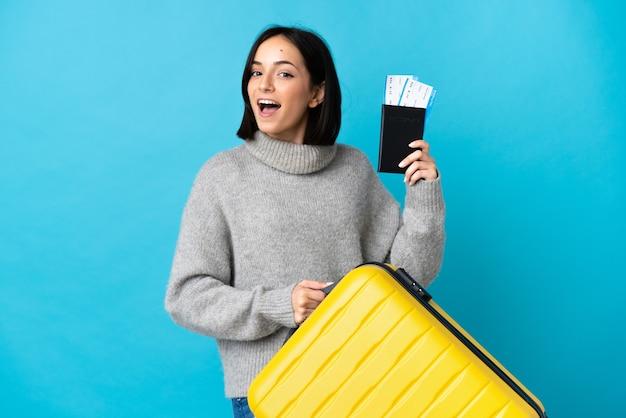 Giovane donna caucasica isolata sull'azzurro in vacanza con la valigia e il passaporto