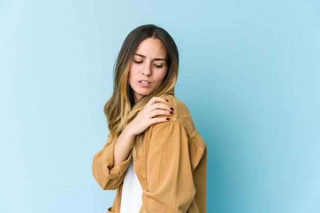 Giovane donna caucasica isolata sulla parete blu che ha un dolore alla spalla.