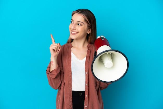Giovane donna caucasica isolata sulla parete blu che tiene un megafono e che intende realizzare la soluzione