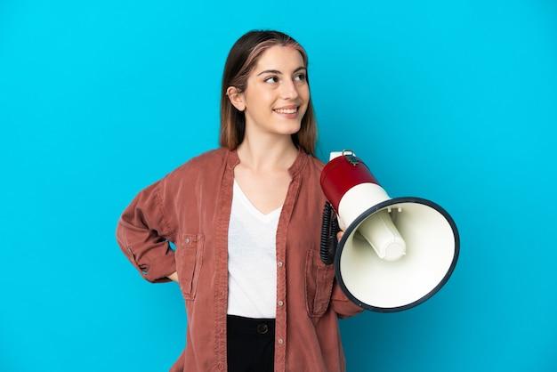 Giovane donna caucasica isolata sulla parete blu che tiene un megafono e che osserva in su mentre sorride