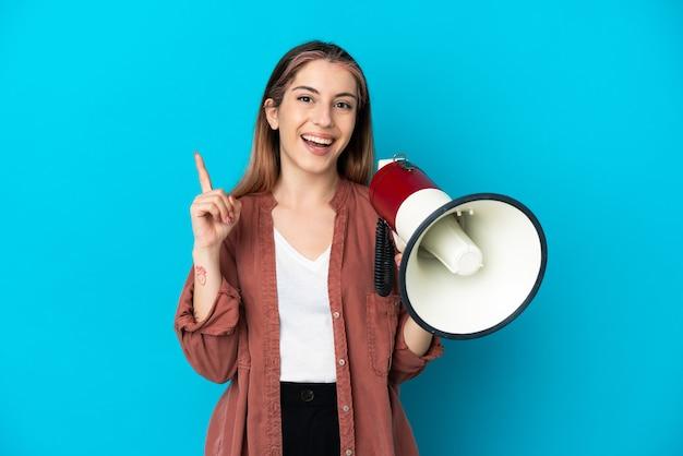 Giovane donna caucasica isolata sulla parete blu che tiene un megafono e che indica una grande idea