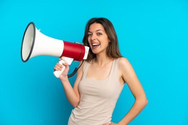 Giovane donna caucasica isolata sulla parete blu che tiene un megafono e che sorride