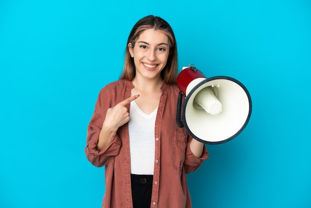 Giovane donna caucasica isolata sulla parete blu che tiene un megafono e con l'espressione facciale di sorpresa