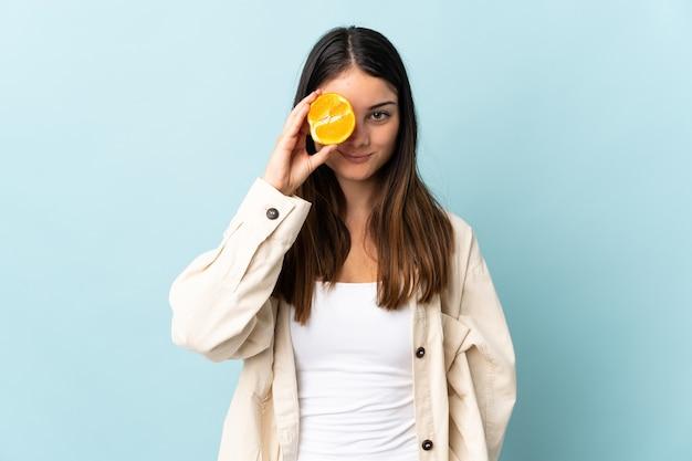 Giovane donna caucasica isolata sulla parete blu che tiene un'arancia