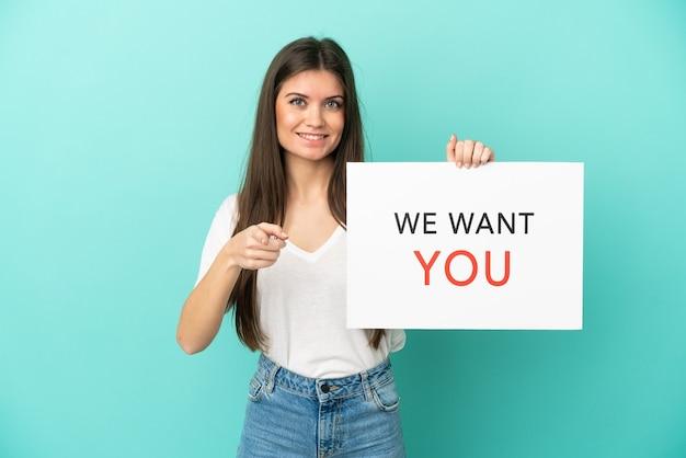 Giovane donna caucasica isolata sulla parete blu che tiene la scheda di we want you e che indica la parte anteriore