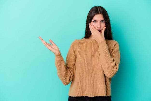 La giovane donna caucasica isolata sulla parete blu tiene lo spazio della copia su una palma, tiene la mano sulla guancia. stupito e deliziato.