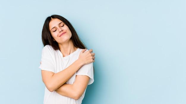 Giovane donna caucasica isolata sugli abbracci blu della parete, sorridente spensierata e felice.