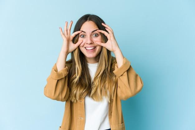 Giovane donna caucasica isolata sulla parete blu che tiene gli occhi aperti per trovare un'opportunità di successo.