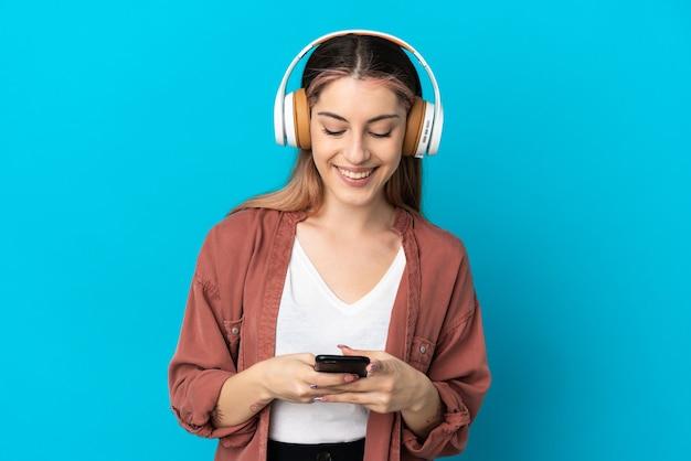Giovane donna caucasica isolata sulla parete blu che ascolta musica e che osserva al cellulare