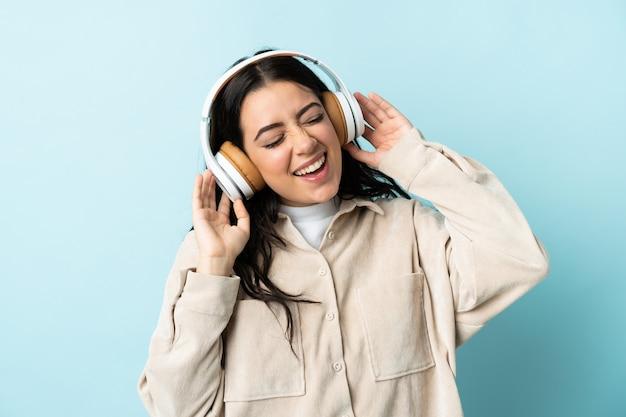 Giovane donna caucasica isolata sulla parete blu che ascolta musica e canto