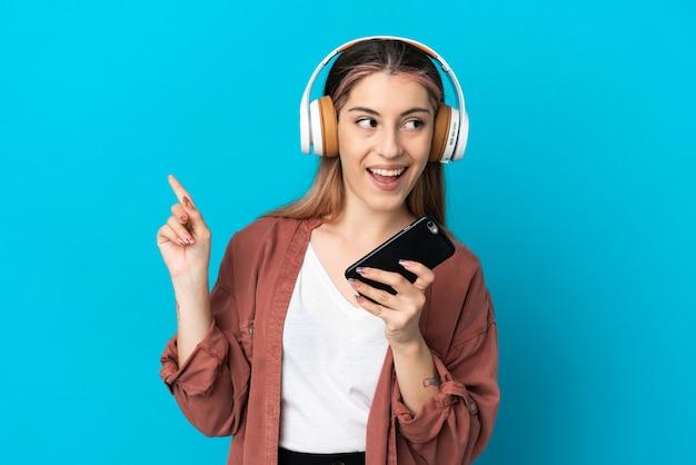 Giovane donna caucasica isolata sulla musica d'ascolto della parete blu con un cellulare e cantando