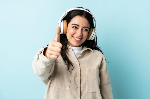 Giovane donna caucasica isolata sulla musica d'ascolto della parete blu e con il pollice in su