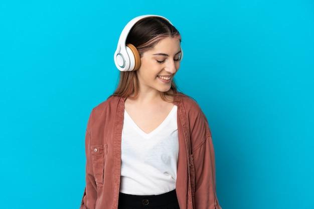 Giovane donna caucasica isolata sulla musica d'ascolto della parete blu