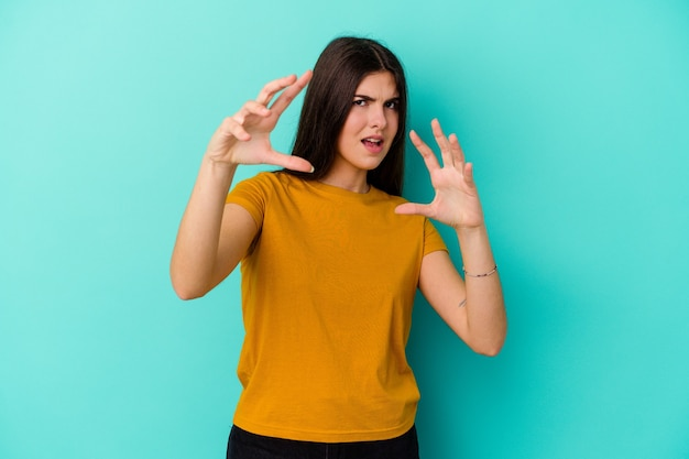 Giovane donna caucasica isolata sulla parete blu che mostra gli artigli che imitano un gatto, gesto aggressivo.