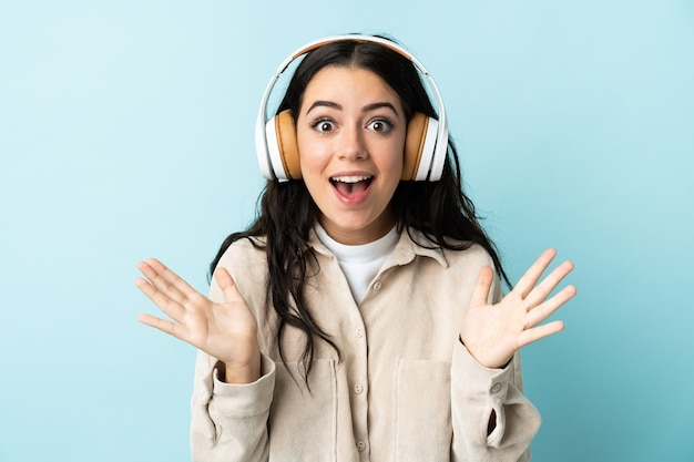 Giovane donna caucasica isolata sulla parete blu sorpresa e musica d'ascolto