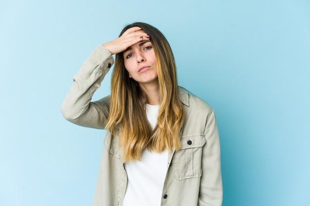 Giovane donna caucasica isolata sulla parete blu che tocca le tempie e che ha mal di testa.