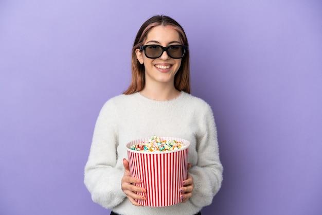 Giovane donna caucasica isolata sulla parete blu con gli occhiali 3d e che tiene un grande secchio di popcorn