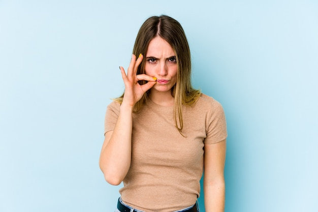 Giovane donna caucasica isolata sulla parete blu con le dita sulle labbra mantenendo un segreto.