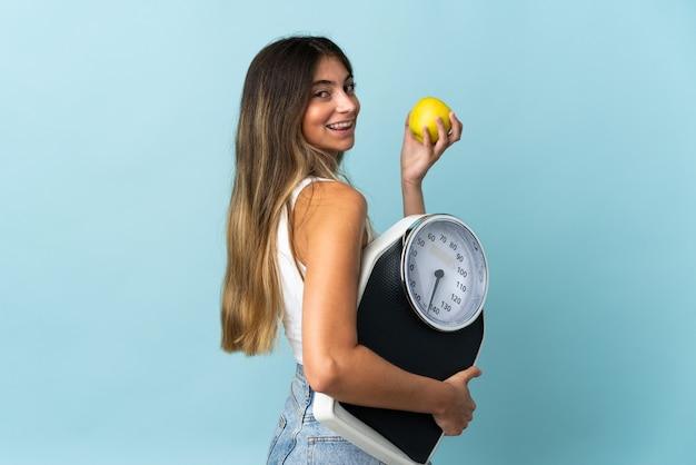 Giovane donna caucasica isolata sulla parete blu con pesatrice e con una mela