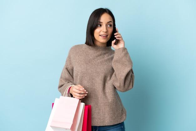 La giovane donna caucasica ha isolato i sacchetti della spesa della tenuta e chiama un amico con il suo telefono cellulare