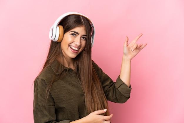 La giovane donna caucasica ha isolato la musica d'ascolto e fa il gesto della chitarra