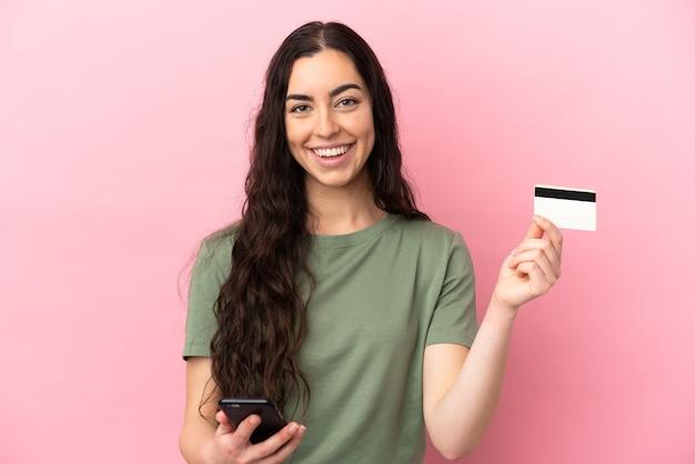 Giovane donna caucasica isolata su sfondo rosa che acquista con il cellulare con una carta di credito