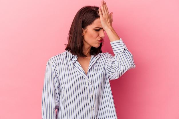 Giovane donna caucasica isolata su sfondo rosa dimenticando qualcosa, schiaffeggiando la fronte con il palmo e chiudendo gli occhi.