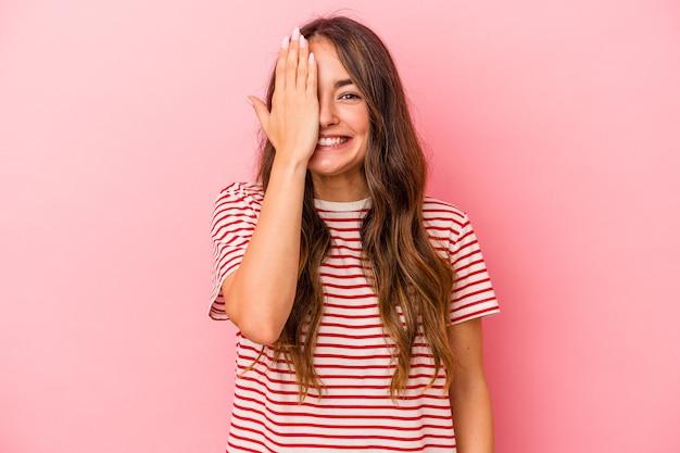 Giovane donna caucasica isolata su sfondo rosa divertendosi coprendo metà del viso con il palmo.