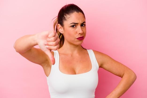 Giovane donna caucasica isolata su sfondo rosa con mal di testa, toccando la parte anteriore del viso.