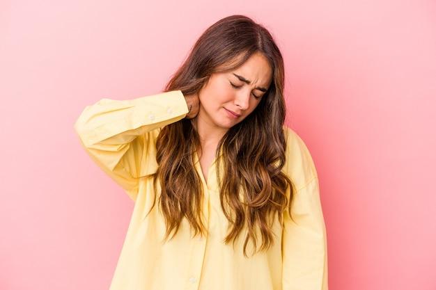 Giovane donna caucasica isolata su sfondo rosa con dolore al collo dovuto allo stress, massaggiandolo e toccandolo con la mano.