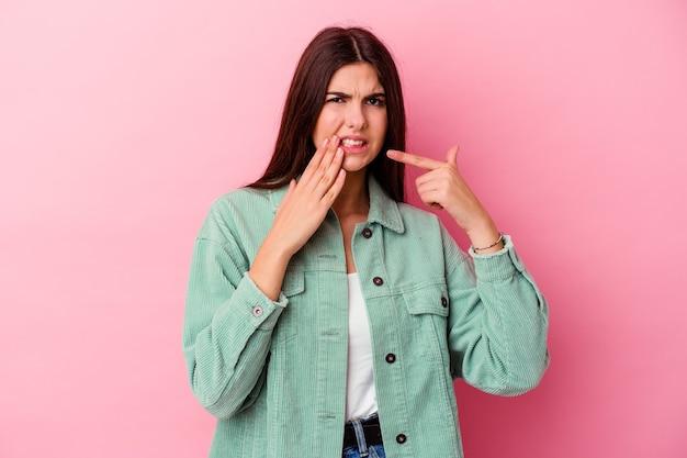 Giovane donna caucasica isolata su sfondo rosa con un forte dolore ai denti, dolore molare.