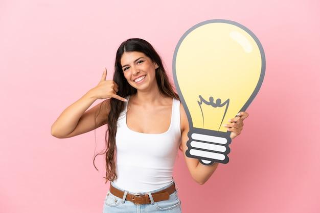 Giovane donna caucasica isolata su sfondo rosa che tiene in mano un'icona a forma di lampadina e fa il gesto del telefono