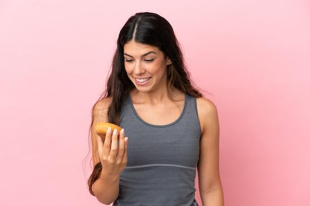 Giovane donna caucasica isolata su sfondo rosa con ciambelle con espressione felice