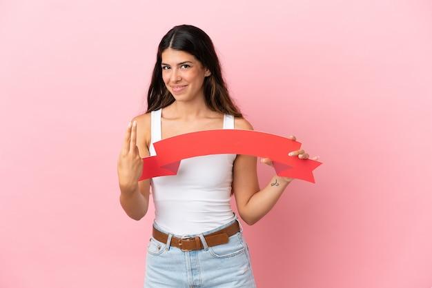 Giovane donna caucasica isolata su sfondo rosa con in mano un cartello vuoto e facendo un gesto imminente