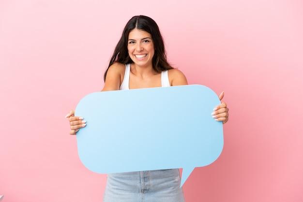 Giovane donna caucasica isolata su sfondo rosa in possesso di un fumetto vuoto con espressione sorpresa
