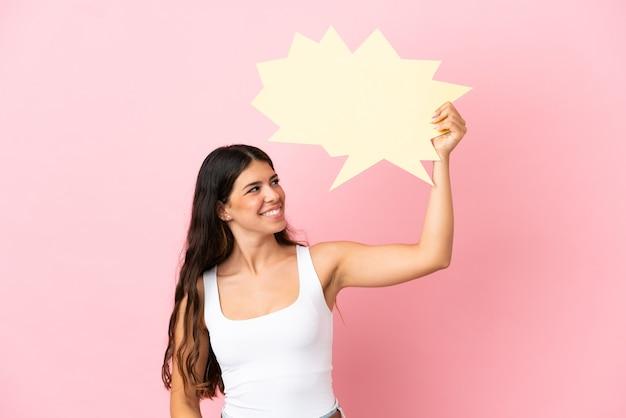 Giovane donna caucasica isolata su sfondo rosa con in mano un fumetto vuoto