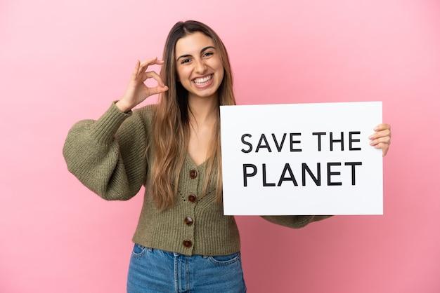 Giovane donna caucasica isolata su sfondo rosa che tiene un cartello con il testo salva il pianeta e celebra una vittoria