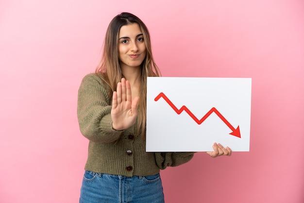 Giovane donna caucasica isolata su sfondo rosa con in mano un cartello con un simbolo di freccia di statistiche decrescenti e facendo il segnale di stop
