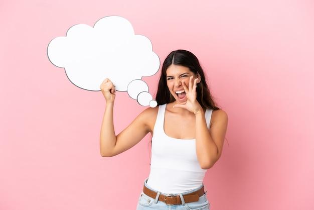 Giovane donna caucasica isolata su sfondo rosa che tiene in mano un fumetto pensante e urla