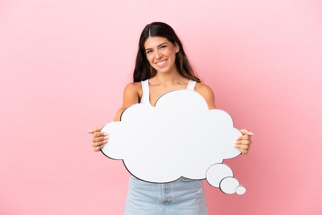 Giovane donna caucasica isolata su sfondo rosa con in mano un fumetto pensante