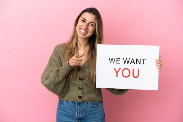 Giovane donna caucasica isolata su sfondo rosa, tenendo la scheda we want you e indicando la parte anteriore
