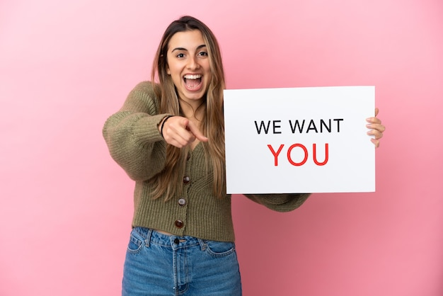 Giovane donna caucasica isolata su sfondo rosa, azienda we want you board e punta verso la parte anteriore