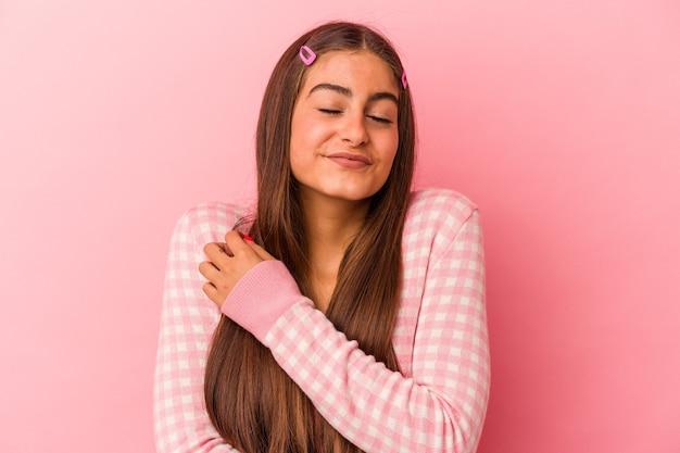 La giovane donna caucasica isolata sugli abbracci rosa del fondo, sorride spensierata e felice.