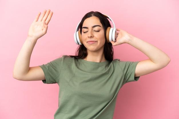 Giovane donna caucasica isolata su sfondo rosa ascoltando musica e ballando