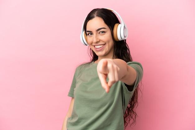 Giovane donna caucasica isolata su sfondo rosa ascoltando musica e indicando la parte anteriore