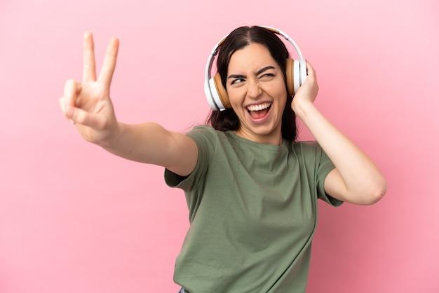 Giovane donna caucasica isolata su sfondo rosa ascoltando musica e cantando